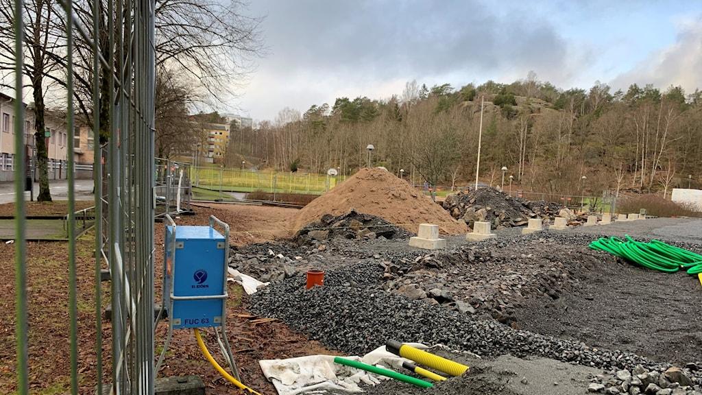 En byggarbetsplats i kanten mellan ett bostadsområde och ett skogsbryn.