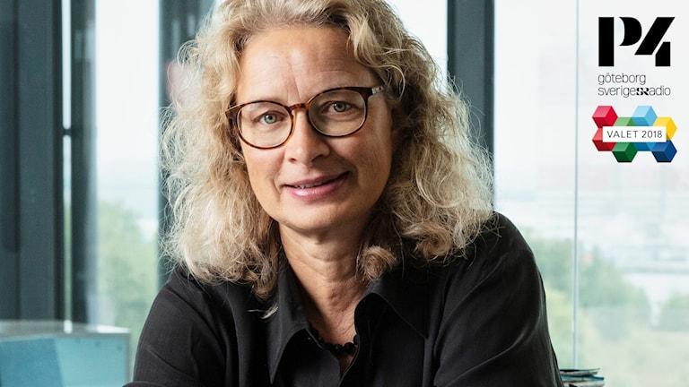 En kvinna med långt lockigt hår och glasögon.