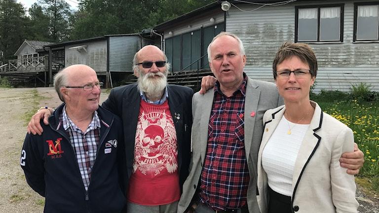 Fyra personer framför en sliten träbyggnad.