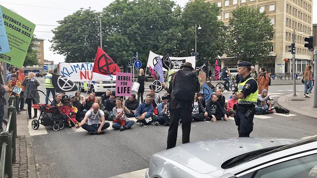 Människor sitter mitt i gatan och stoppar trafiken med flaggor och banderoller.