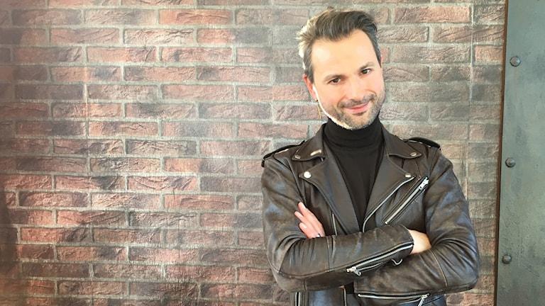 En mörkhårig man med svart skinnjacka