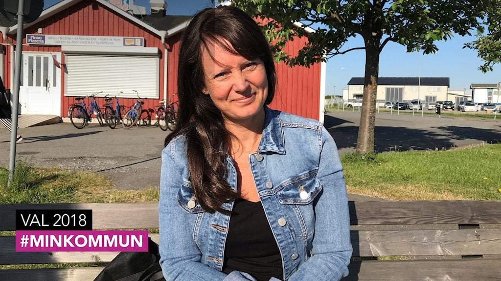En kvinna med långt brunt hår, klädd i jeansjacka sitter utomhus på en träbänk.