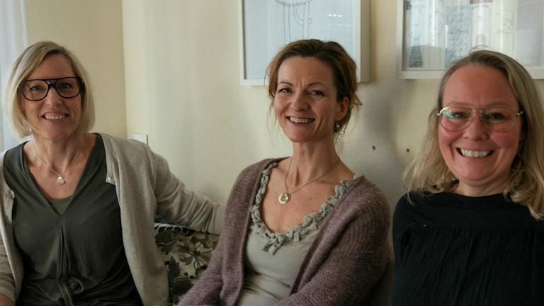 Tre leende kvinnor sitter i en soffa