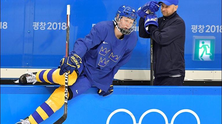 en ishockeyspelare klättrar över rinksargen