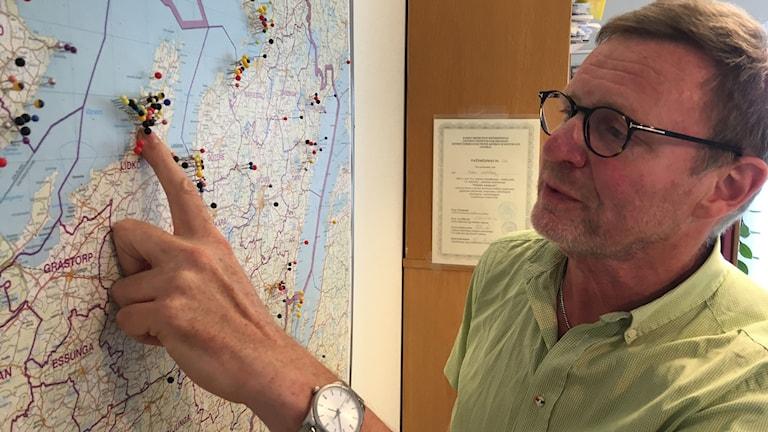 Läkaren pekar med fingret på en karta med nålar som visar olika punkter.