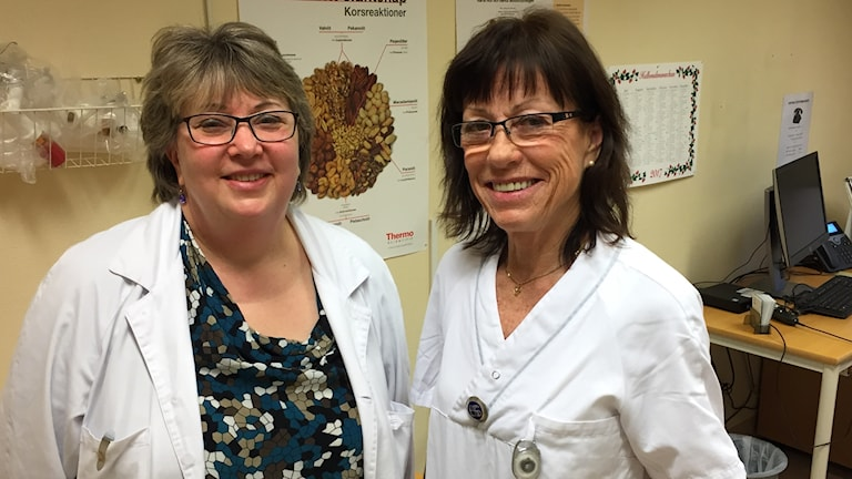 Överläkaren Monica Arvidsson och biträdande vårdenhetschefen Ulrika Andreasson vid Sahlgrenskas allergimottagning med plansch på allergiframkallande nötter i bakgrunden
