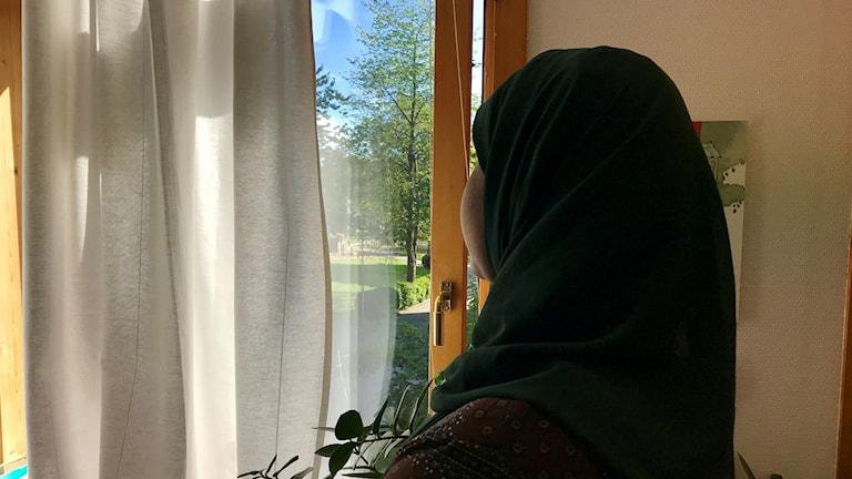 Kvinna i slöja/hajib tittar ut genom fönster.