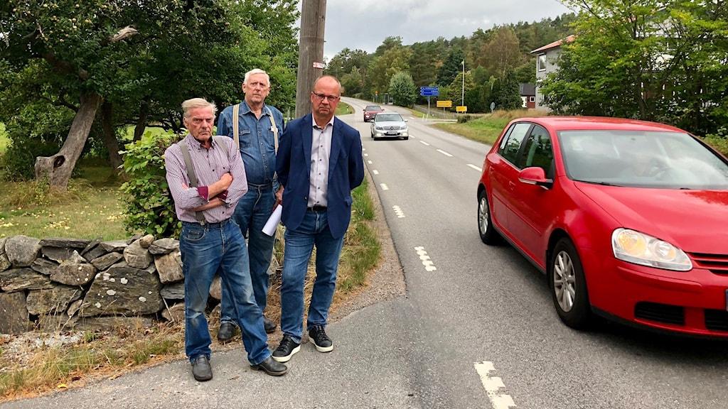 Tre män står vid en väg där det kommer bilar.