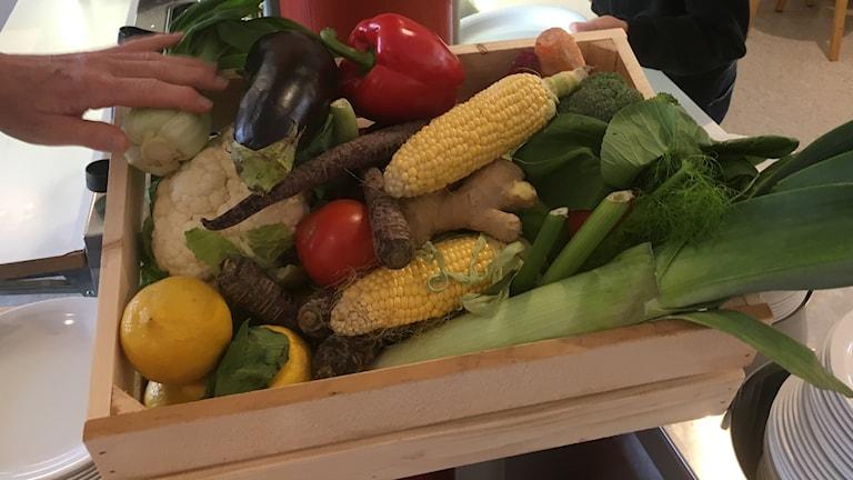 En trälåda med grönsaker