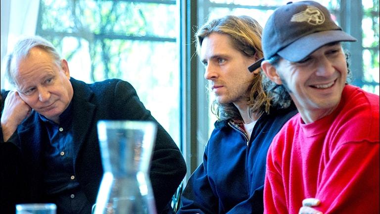 Tre män som sitter vid ett bord