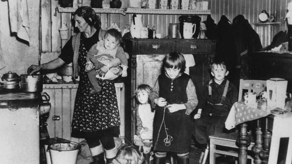 Kvinna i förkläde och med barn på armen står vid spisen och lagar mat .