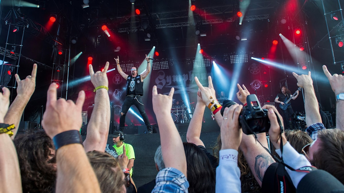 En publik gör djävulstecken med händerna mot scenen där ett band uppträder.