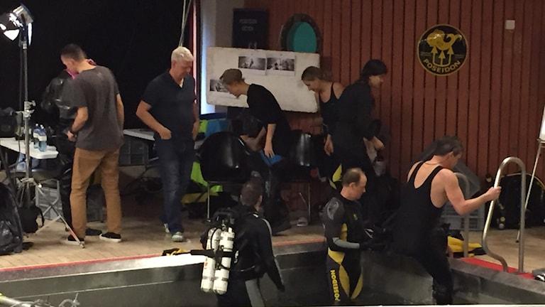 Filminspelning Breaking Surface . En av skådespelarna och dykare kliver ur poolen och annan personal är på poolkanten