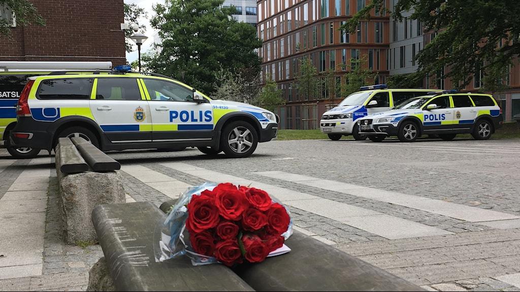 Blommor som ligger framför polisbilar.