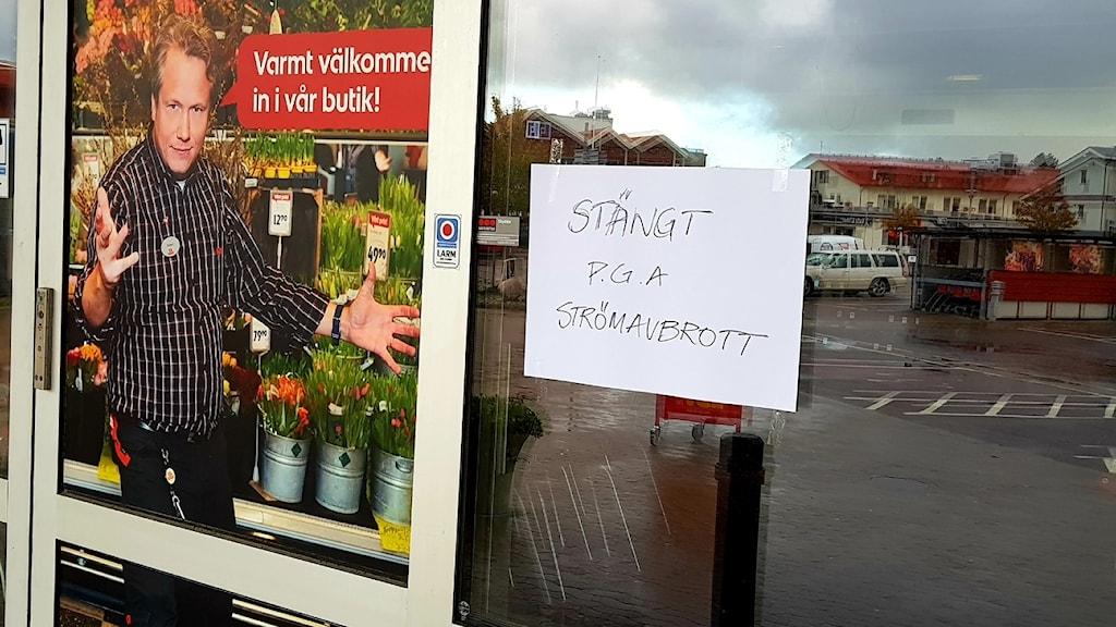 """En affärsdörr där det står """"Stängt på grund av Strömavbrott""""."""