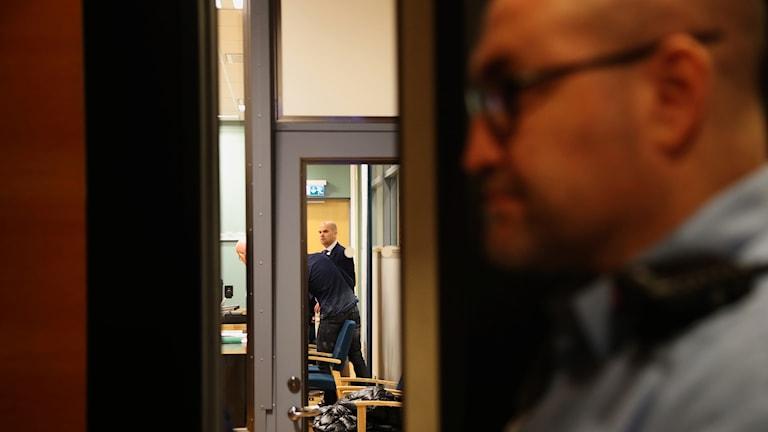 En polis står utanför rättssalen.