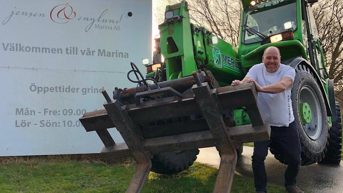 Man i vit t-shirt vid grön traktor