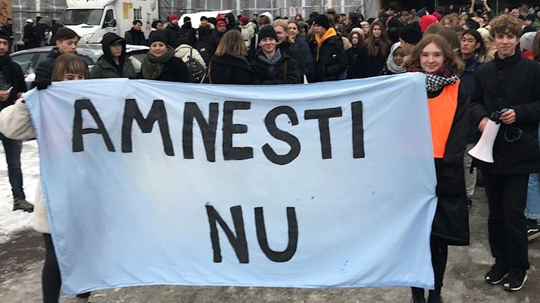 """Ungdomar med en banderoll med texten: """"AMNESTI NU""""."""
