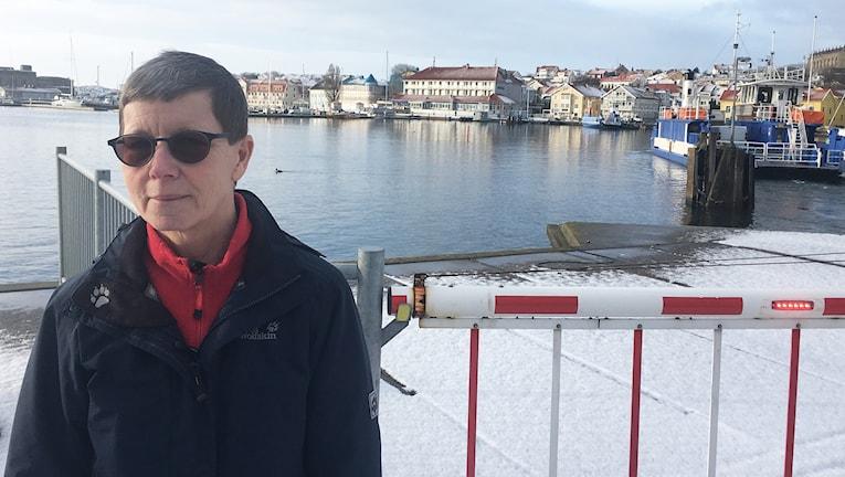 En kvinna står vd färjeläget på Koön. I bakgrunden syns Marstrandsön och hotell Oscars.