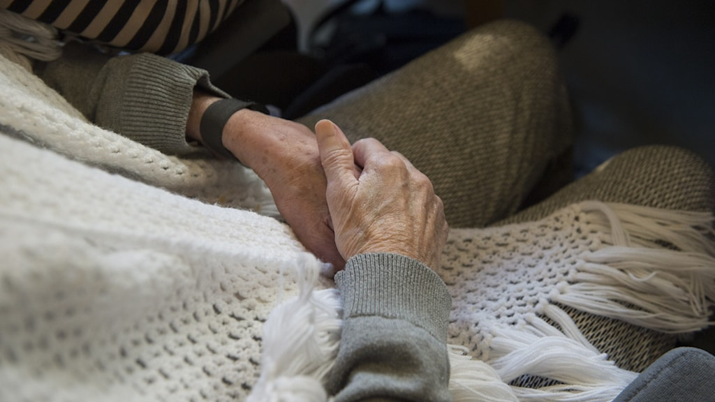 Äldre händer vilar på en filt.