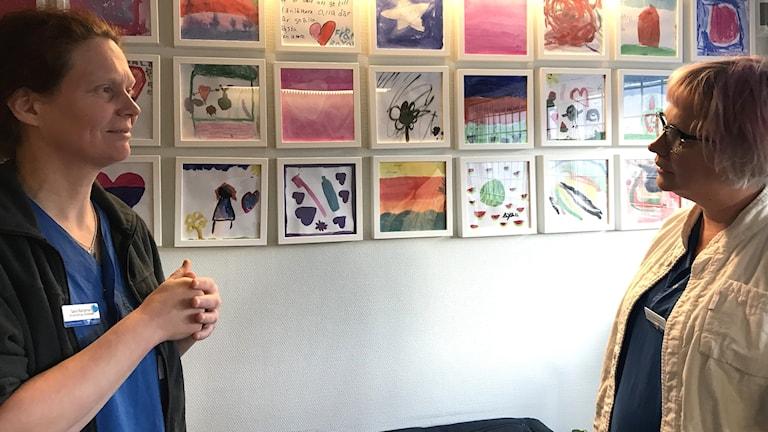 Två kvinnor tittar på varandra, mellan dem syns en vägg med färgglada teckningar