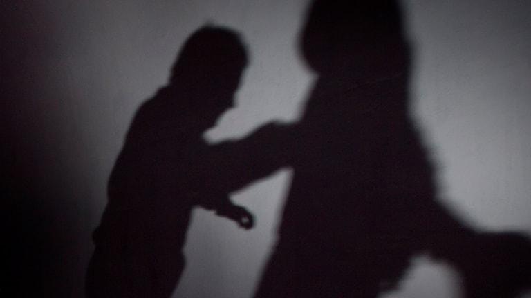Två personer syns som skuggor mot en vägg.