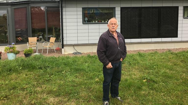 Hans-Olof Nilsson framför sitt hus som bär solpanel både på väggar och tak.