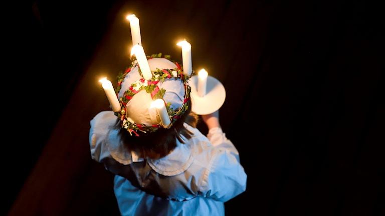 En Lucia klädd i vitt med ljus i håret.