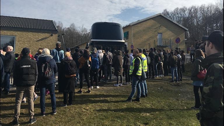 Människor står runt en buss.