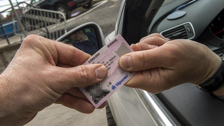 En person håller fram sitt körkort genom fönstret på bilen och en annan person tar tag i det.