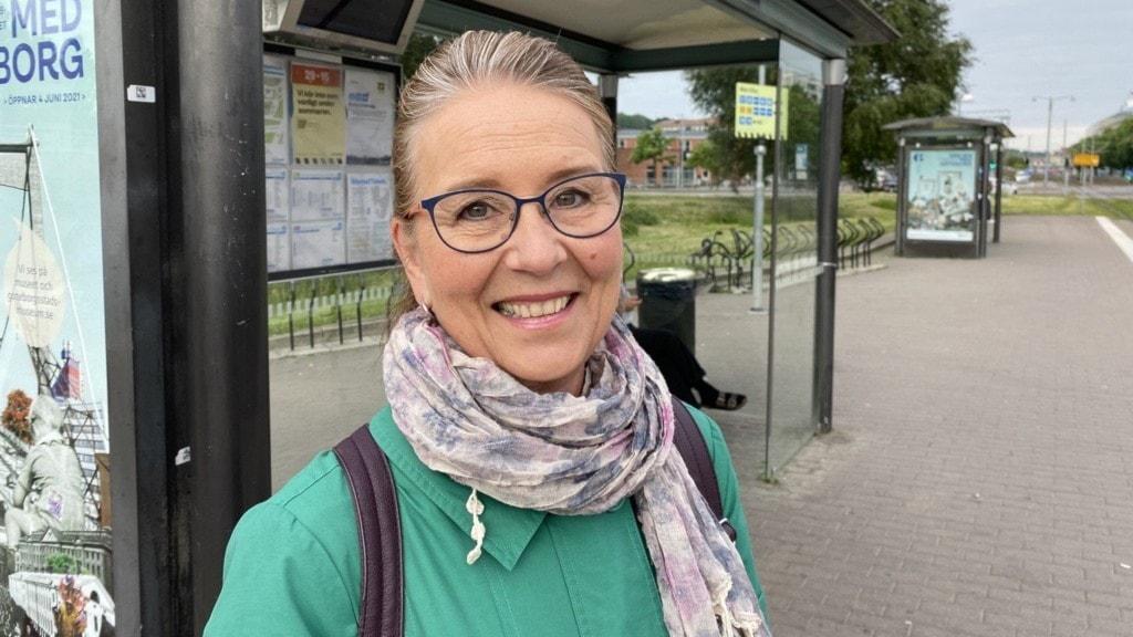 kvinna i grön tröja vid busshållplats