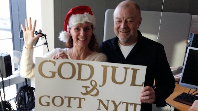 Två personer och ett stort plakat där det står god jul och gott nytt