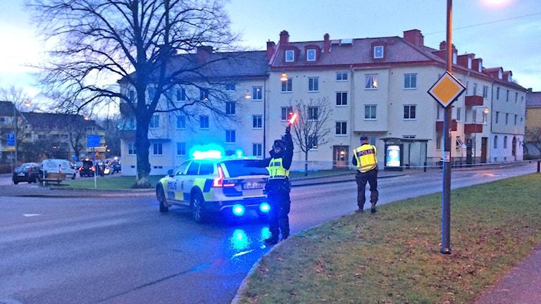 Bil med blåljus och poliser som stoppar trafik