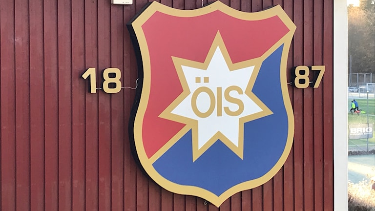 ÖIS blå-röda klubbmärke på väggen till klubbhuset. Siffrorna 1887 står i guldfärg.