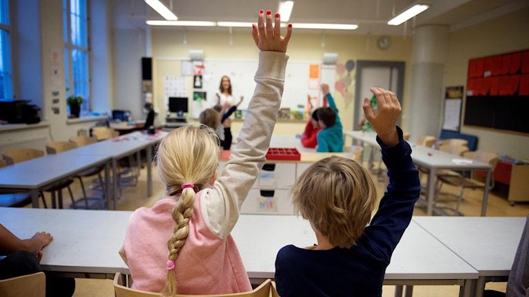 Barn som räcker upp handen