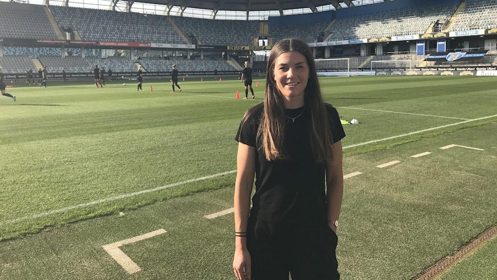 En tjej med långt brunt hår står vid sidan om fotbollsplanen på Gamla Ullevi. Bakom henne tränas det fotboll.
