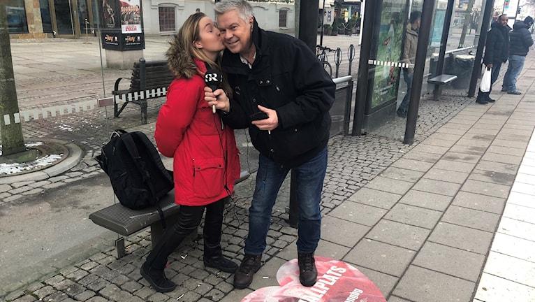 """En kvinna pussar en man på kinden vid en busshållplats. På marken finns ett hjärta med texten """"pusshållplats""""."""