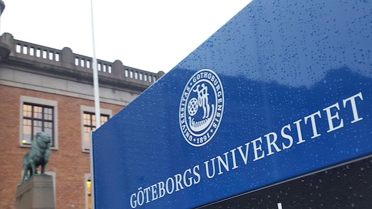 """Skylt framför huvudbyggnaden med text """"Göteborgs Universitet""""."""