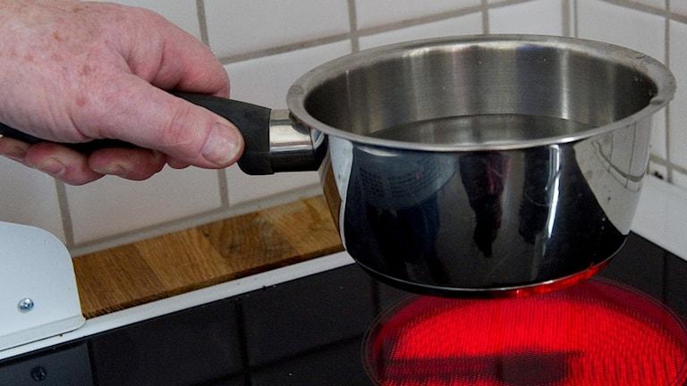 En hand håller i en kastrull med vatten ovanför en varm spisplatta.