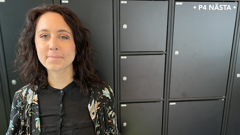 Sara står mot en vägg av svarta, låsbara skåp. Hon har axellångt, mörkbrunt hår. Ler lite med stängd mun.
