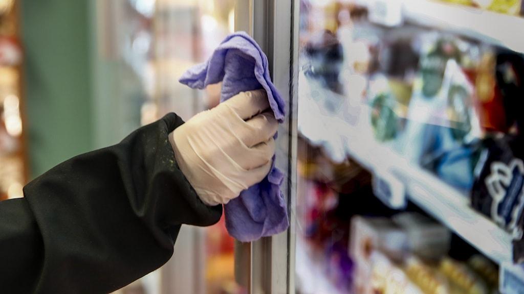 Hand med handske som torkar av handtag