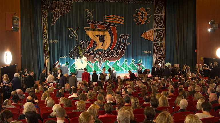 Människor sitter i biosalongen Draken där draperiet med bild på ett vikingaskepp är fördraget framför bioduken.
