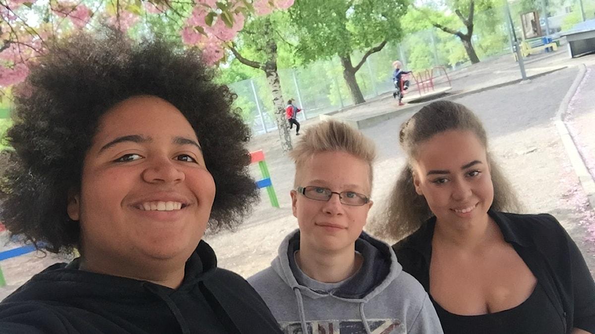 Kasiluokkalaiset Jasper, Erik ja Nadine seisovat koulun pihalla.