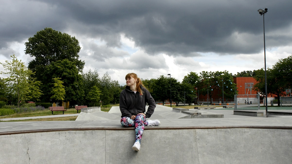 Emilia Ovaska istuu skeittirampin reunalla.
