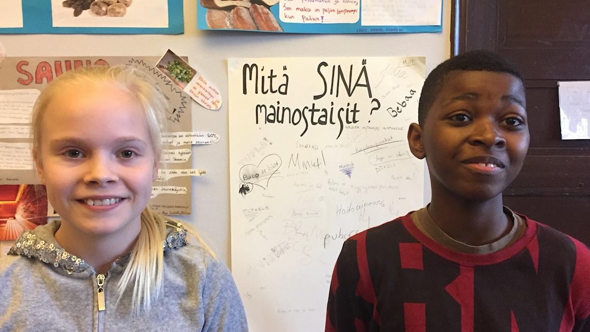 Mia Malin ja Tresor Mayunga Ndongo katsovat kameraan, niiden takana on kyltti missä lukee: mitä sinä sanoisit?