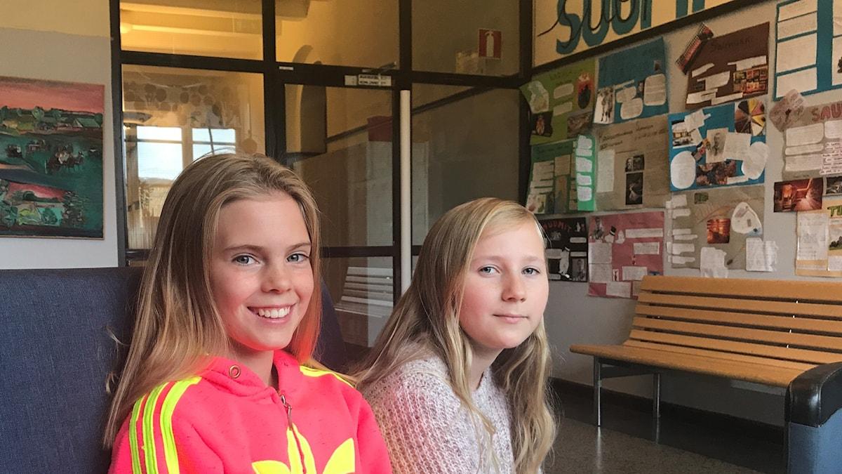 Oliva Holmström ja Aurora Westin istuvat sohvassa ja katsovat kameraan.