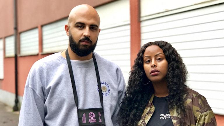 En man och en kvinna poserar framför en vägg.