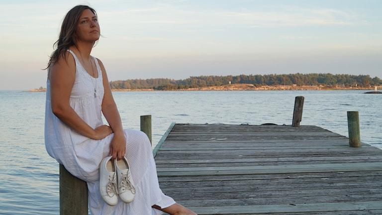 En bild där Natasha Nilsson sitter i vit klänning på en brygga.