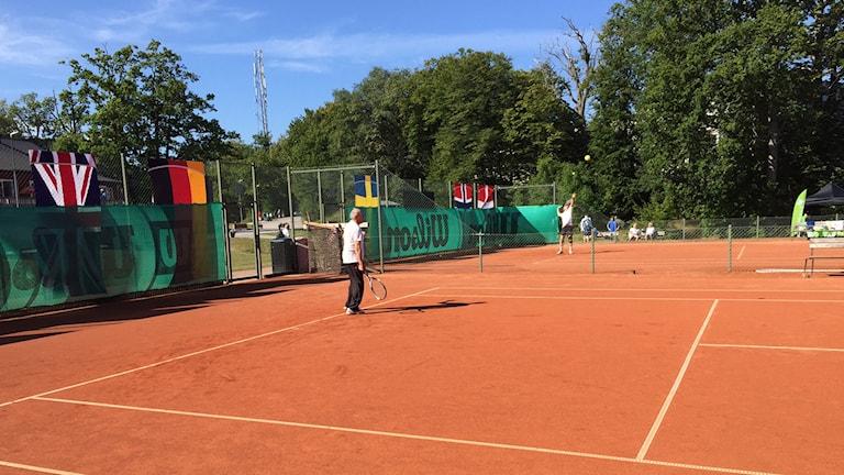 En pågående tennismatch mellan två spelare på en röd grusplan.