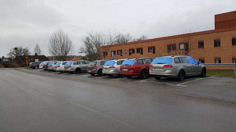 Bilar vid sjukhuset med blåa draperier över flera fönster.